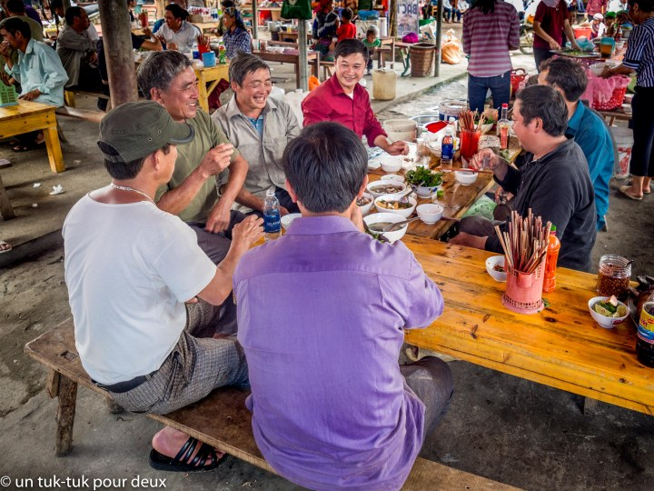 Les hommes prennent quelques verre d'alcool de riz au marché de Bac Ha